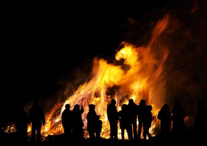 Crowds watch a bonfire