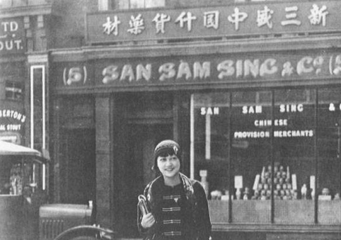 A young woman leaves a shop in Chinatown, Limehouse